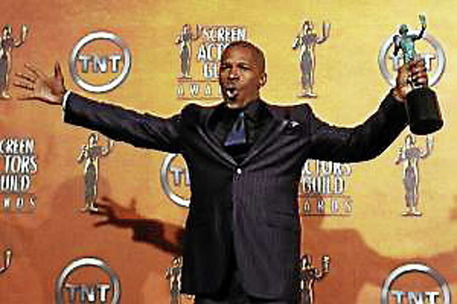 "Jamie Foxx holds the award for outstanding performance by a male actor in a leading role for his work in ""Ray, "" backstage at the 11th annual Screen Actors Guild Awards on Saturday, Feb. 5, 2005, in Los Angeles. Photo: (Chris Pizzello — The Associated Press)"