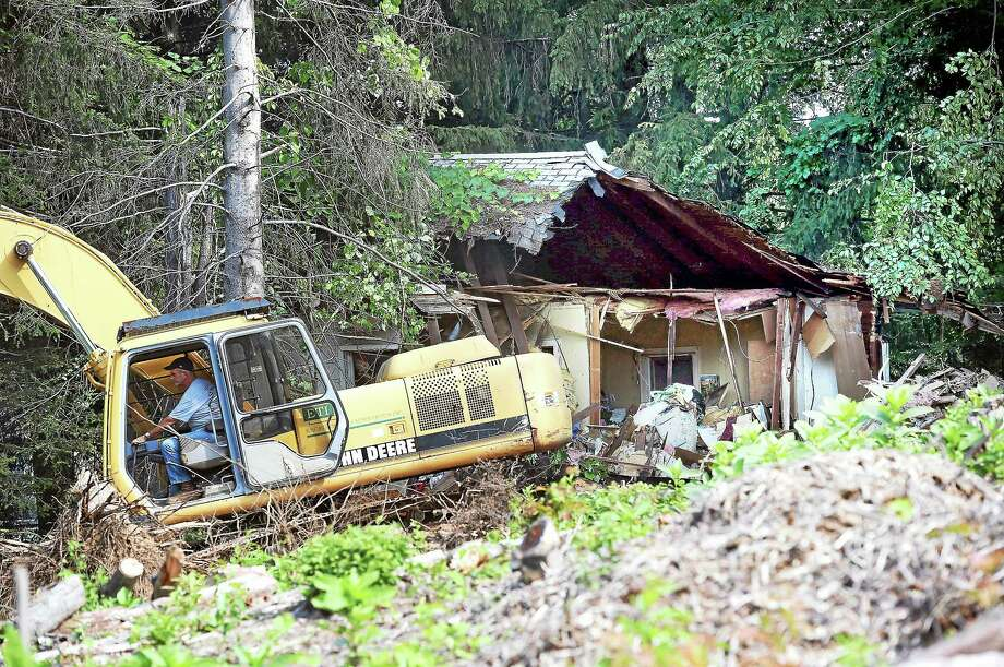 An excavator clears debris into dumpsters during demolition of the home of the late Beverly Mitchell in Cheshire Thursday. Photo: Arnold Gold — New Haven Register