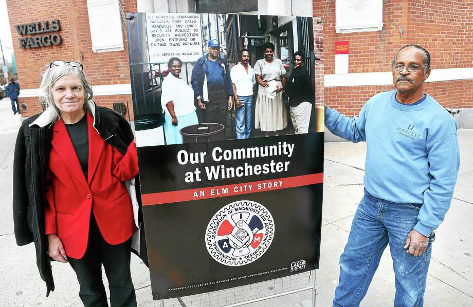 Joan Cavanagh, left, director of the Greater New Haven Labor History Association, and Craig Gauthier, former president of Local 609 of the International Association of Machinists, hold one of the panels of an exhibit on Olin-Winchester labor history, outside Wells Fargo Bank in New Haven. Gauthier is at the center of the panel's photograph, along with, from left, Tina Tally, Emmanuel Gomez, Georgianna Coleman and Cicelia Leakes. Photo: Arnold Gold — New Haven Register