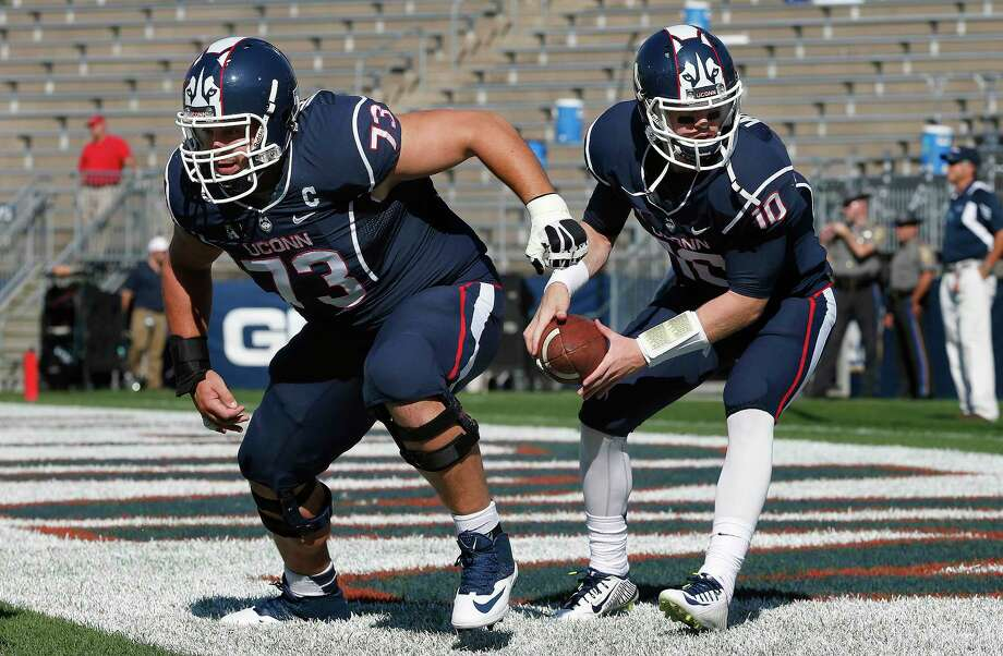 Connecticut offensive linesman Alex Mateas (73) runs drills with quarterback Chandler Whitmer (10) before an NCAA college football game against Temple in East Hartford, Conn., Saturday, Sept. 27, 2014. (AP Photo/Michael Dwyer) Photo: AP / AP
