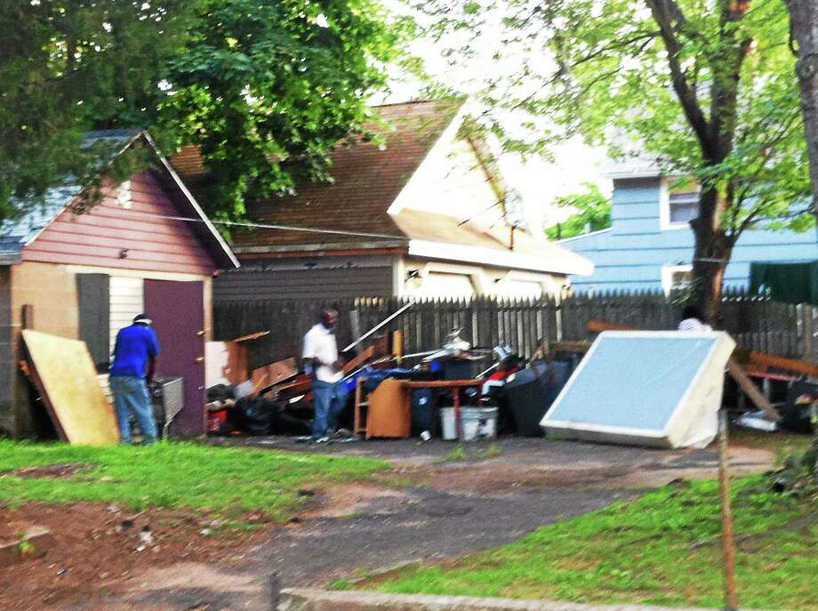 KELDY ORTIZ — NEW HAVEN REGISTER  Landlord Kelly Moye, left, watches as Glenford Jackson puts his clothing and furniture in the garage he and another person had been renting. Photo: Journal Register Co.