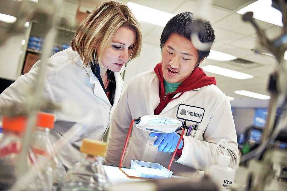 Scientist Guang Liu shows communications associate Courtney Goodwin the purity of an antigen in a FluBlok influenza vaccine at Protein Sciences at 1000 Research Pkwy in Meriden Wednesday, November 26, 2014. Photo: (Catherine Avalone — New Haven Register)    / New Haven RegisterThe Middletown Press