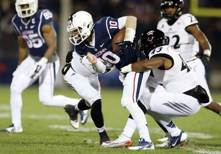 Cincinnati linebacker Nick Temple (43) tackles UConn quarterback Chandler Whitmer during last Saturday's game at Rentschler Field in East Hartford. Photo: Michael Dwyer — The Associated Press   / AP