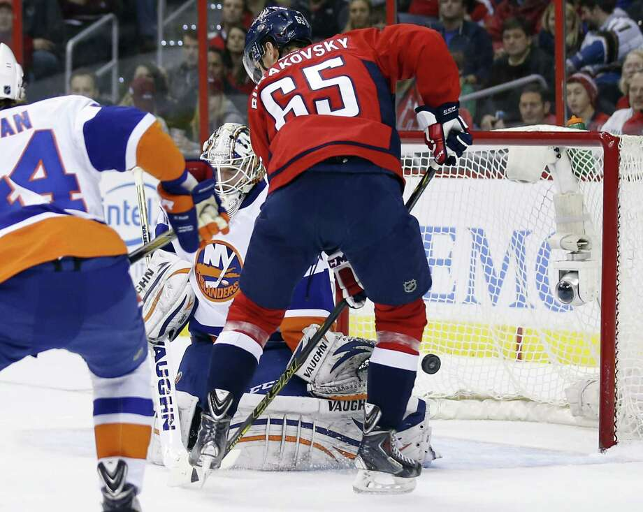 New York Islanders goalie Chad Johnson can't stop a goal by Washington defenseman Matt Niskanen (not shown) with Capitals left wing Andre Burakovsky (65) nearby during the Capitals' 5-2 win on Friday in Washington. Photo: Alex Brandon — The Associated Press   / AP