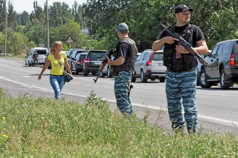 Self-proclaimed Donetsk People's Republic policemen guard a convoy of international forensic experts, Dutch and Australian policemen and members of the Organization for Security and Cooperation in Europe mission in Ukraine, as it approached Shakhtarsk, Donetsk region, eastern Ukraine, on Monday, July 28, 2014. An international police team abandoned its attempt to reach the crash site of a Malaysia Airlines plane for a second day running Monday as clashes raged in a town on the road to the area. (AP Photo/Dmitry Lovetsky) Photo: AP / AP