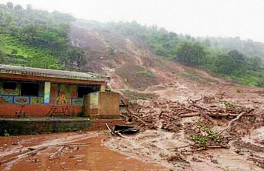 Mud and slush surround a building after a mudslide in Malin village, in the western Indian state of Maharashtra, Wednesday, July 30, 2014. Torrential rains triggered a massive landslide that buried a remote village in western India Wednesday, sweeping away scores of houses and possibly trapping more than 150 people, officials said. (AP Photo/Press Trust of India) INDIA OUT Photo: AP / Press Trust of India (PTI)