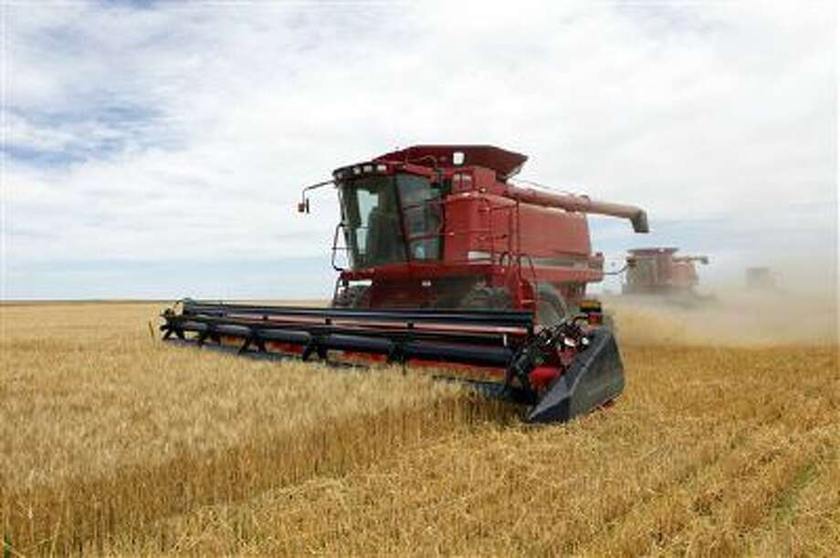 Combines harvest the winter wheat on the Cooksey farm near Roggen, Colo. Photo: ASSOCIATED PRESS / A20092009