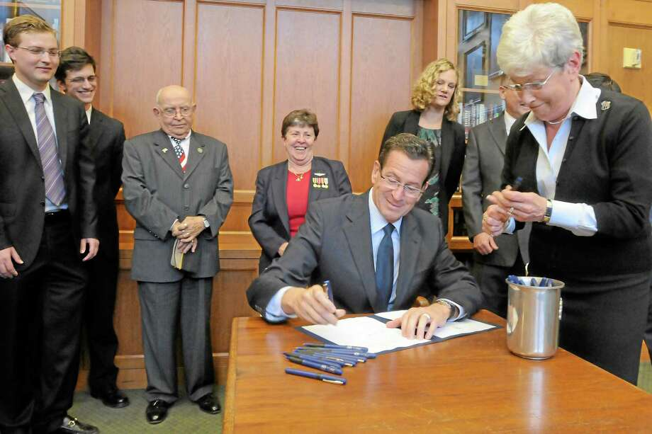 Four bills were passed in 2012 by the Connecticut legislature for new protections for state veterans. In this photo, Gov. Dannel Malloy (with Lt. Gov. Nancy Wyman's help) signs one in a ceremony at the Yale Law School, where students in the school's Veterans Legal Services Clinic were key in calling attention to one of the bills. From left, Yale law students Jon Fougner and Eric Parrie, state Rep. Al Adinolfi, Department of Veterans Affairs Commissioner Linda Schwartz and Margaret Middleton, executive director of the Connecticut Veterans Legal Center. Photo: MARA LAVITT — NEW HAVEN REGISTER
