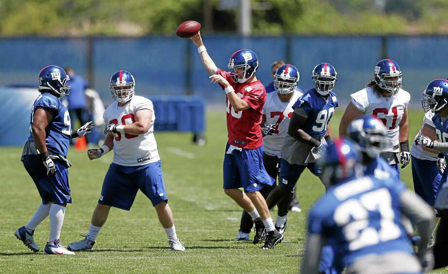 New York Giants quarterback Eli Manning, center, throws a pass during an organized team activity on Thursday in East Rutherford, N.J. Photo: Julio Cortez — The Associated Press   / AP