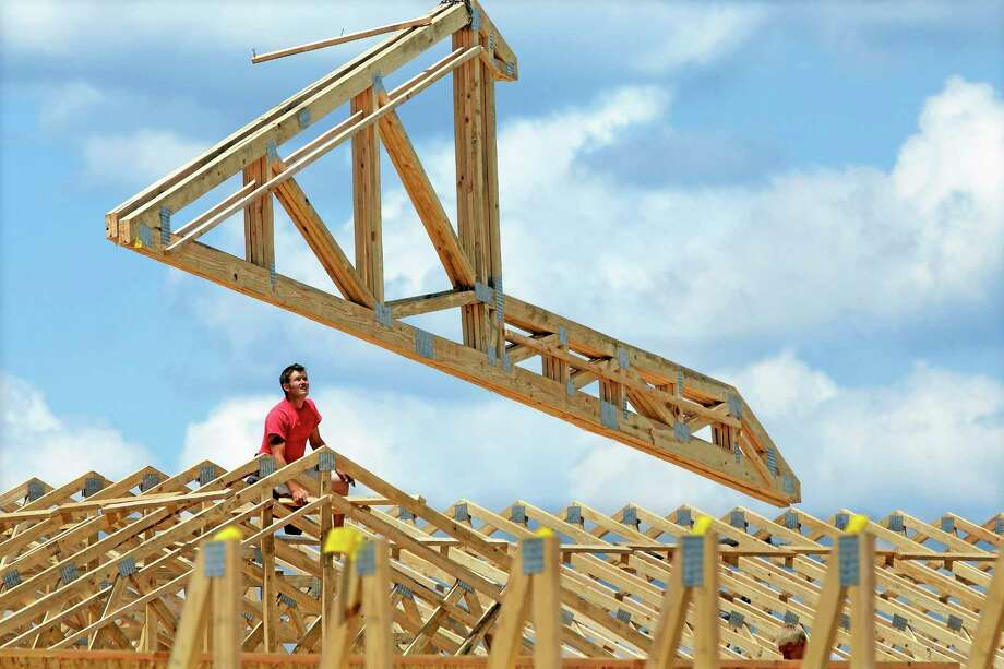 In this July 17, 2014 photo, construction workers build a commercial complex in Springfield, Ill. The government issues its first of three estimates of how fast the U.S. economy grew in the April-June quarter on Wednesday, July 30, 2014. (AP Photo/Seth Perlman) Photo: AP / AP