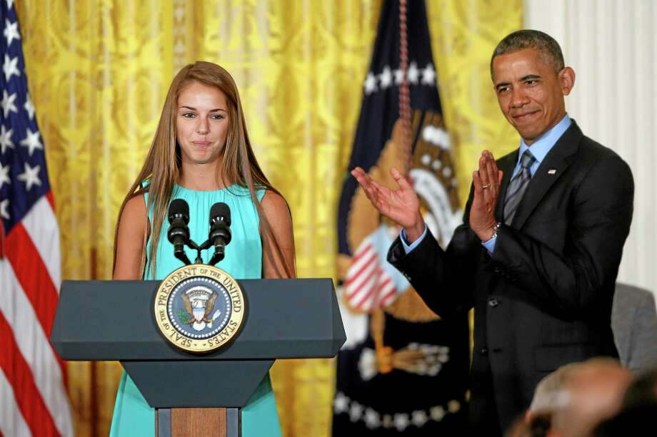President Barack Obama applauds Victoria Bellucci, a 2014 graduate of Huntingtown High Shool in Huntingtown, Md., who suffered five concussions playing soccer, Thursday, May 29, 2014, in the East Room of the White House in Washington, during the White House Healthy Kids and Safe Sports Concussion Summit. Obama was hosting a summit with representatives of professional sports leagues, coaches, parents, young athletes, researchers and others to call attention to the issue of youth sports concussions. (AP Photo/Charles Dharapak) Photo: AP / AP