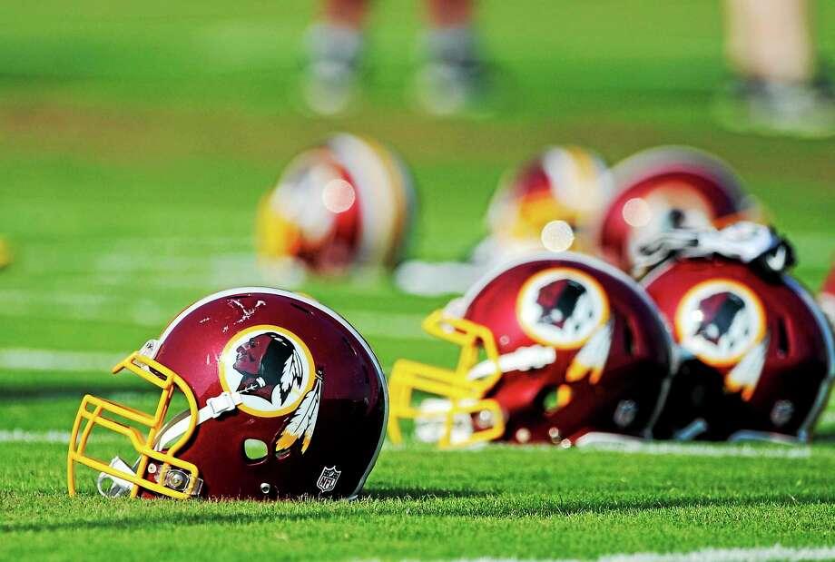 Washington Redskins helmets sit on the field during an NFL football minicamp in Ashburn, Virginia. Photo: Nick Wass — The Associated Press   / AP2014