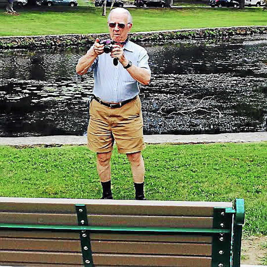 Longtime Milford city historian Richard Platt takes a photo Wednesday of a bench dedicated in his honor on the banks of the North Street Duck Pond.  Photo/Pam McLoughlin Photo: Journal Register Co.