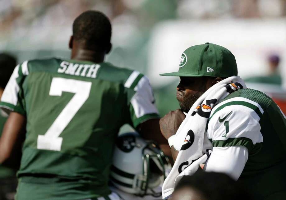 Frank Franklin II — The Associated Press  Jets quarterback Michael Vick, right, sits on the bench near quarterback Geno Smith during the second half Sunday. Photo: AP / AP