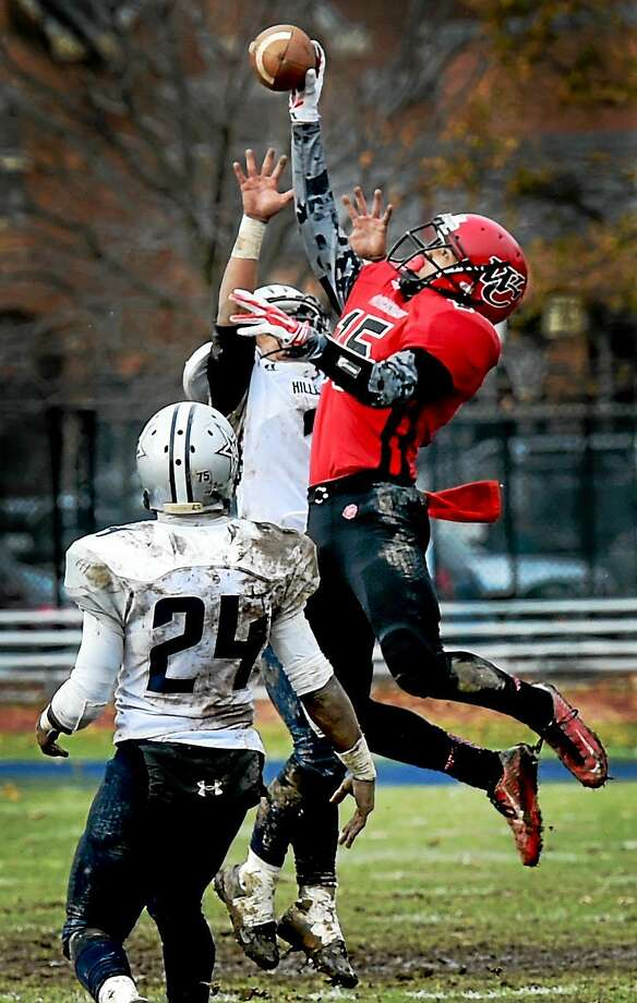(Photo by Peter Hvizdak - New Haven Register)  J.L. Gomez-Stafford of Wilbur Cross H.S. pulls down a pass completion against Kishon Shields and Marlon Hagwood of Hillhouse H.S. during fourth quarter football action at Wilbur Cross H.S. Thursday, November 27, 2014. Photo: ©2014 Peter Hvizdak / ©2014 Peter Hvizdak