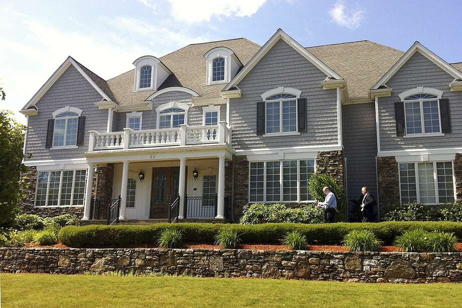 In this June 19, 2013 file photo, two members of the Massachusetts State Police walk toward the front door of the home of New England Patriot's NFL football player Aaron Hernandez in North Attleborough, Mass. Photo: Associated Press   / AP