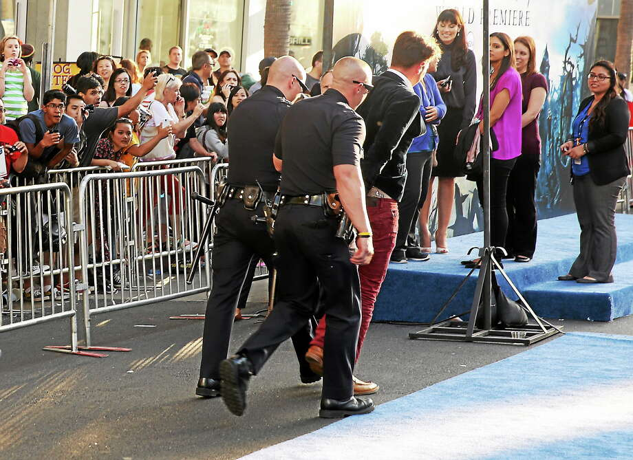 """A fan is walked off carpet in handcuffs after allegedly attacking Brad Pitt at the world premiere of """"Maleficent"""" at the El Capitan Theatre on May 28, 2014, in Los Angeles. Photo: Photo By Matt Sayles/Invision/AP   / Invision"""