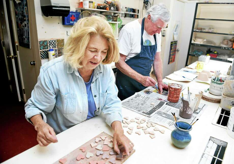 Carol Bell of Clinton and Jay Bowes of Madison paint clay hearts at the Guilford Art Center on 9/19/2014. The hearts are for memory boxes for families of terminally ill patients in the Medical Intensive Care Unit at Yale-New Haven Hospital. Photo: (Arnold Gold — New Haven Register)
