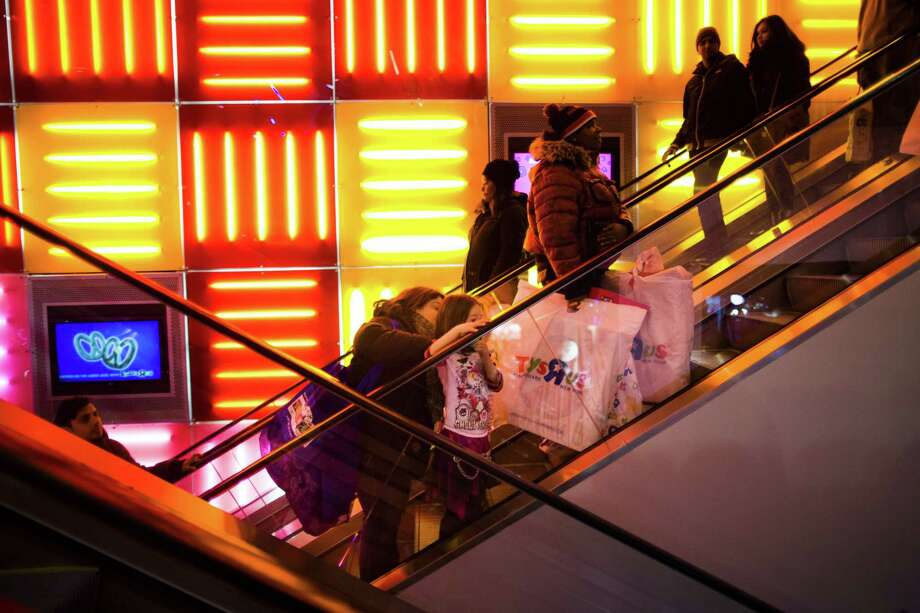 In this Thursday, Nov. 28, 2013 file photo, shoppers ride an escalator at the Times Square Toys R Us, in New York. Millions of Americans are expected to head to the stores for holiday gift shopping on Thanksgiving in whatís quickly becoming a new holiday tradition. Photo: Associated Press   / FR170537 AP