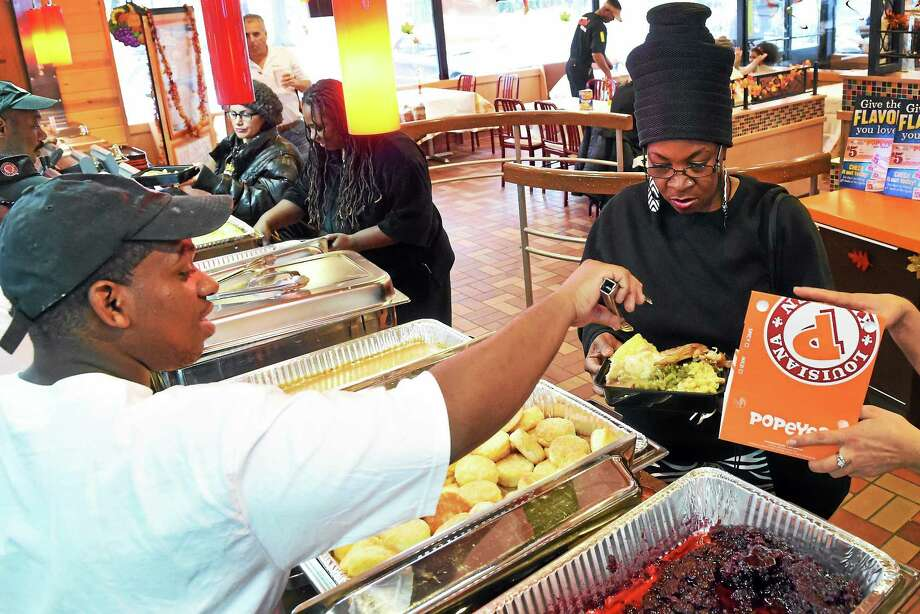 Leon Lewis, left, an employee of Popeyes Louisiana Kitchen restaurant on Whalley Avenue in New Haven, serves food during the restaurant's second annual Thanksgiving Day Feast Thursday. Photo: Peter Hvizdak — New Haven Register    / ©2014 Peter Hvizdak