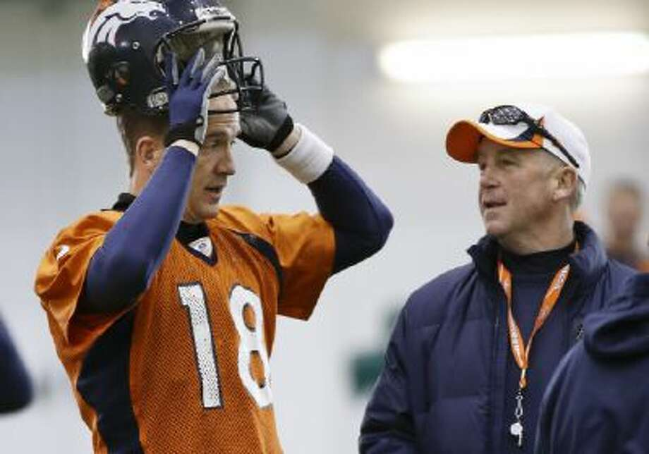 Peyton Manning talks with head coach John Fox during practice Thursday in Florham Park, N.J.