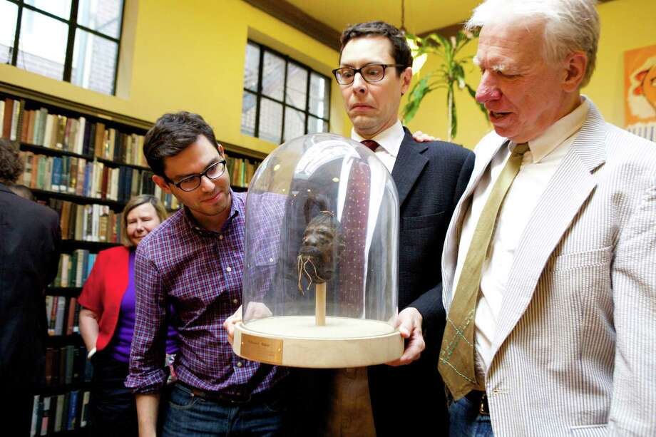 Josh Foer, left, and Jack Hitt, right, conspired to find a shrunken head as a farewell gift to Will Baker, center, departing executive director of The Institute Library. (Photo by Judy Sirota Rosenthal). Photo: Journal Register Co.