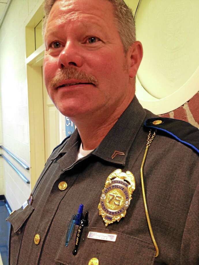 Clinton police Cpl. Craig Lee with the department's 75th anniversary badge. Photo: Stan Fisher — NEW HAVEN REGISTER