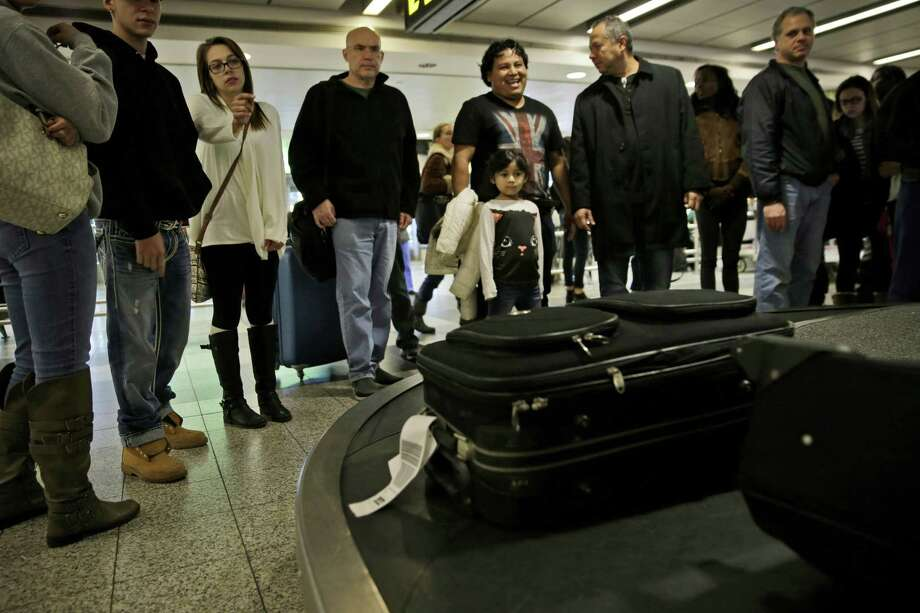 Travelers wait to claim their baggage at LaGuardia Airport in New York Tuesday. A nor'easter was expected to develop along the East Coast just as millions of travelers head to their Thanksgiving destinations, bringing mostly rain close to the coast, but heavier snow further inland. Photo: Associated Press   / AP