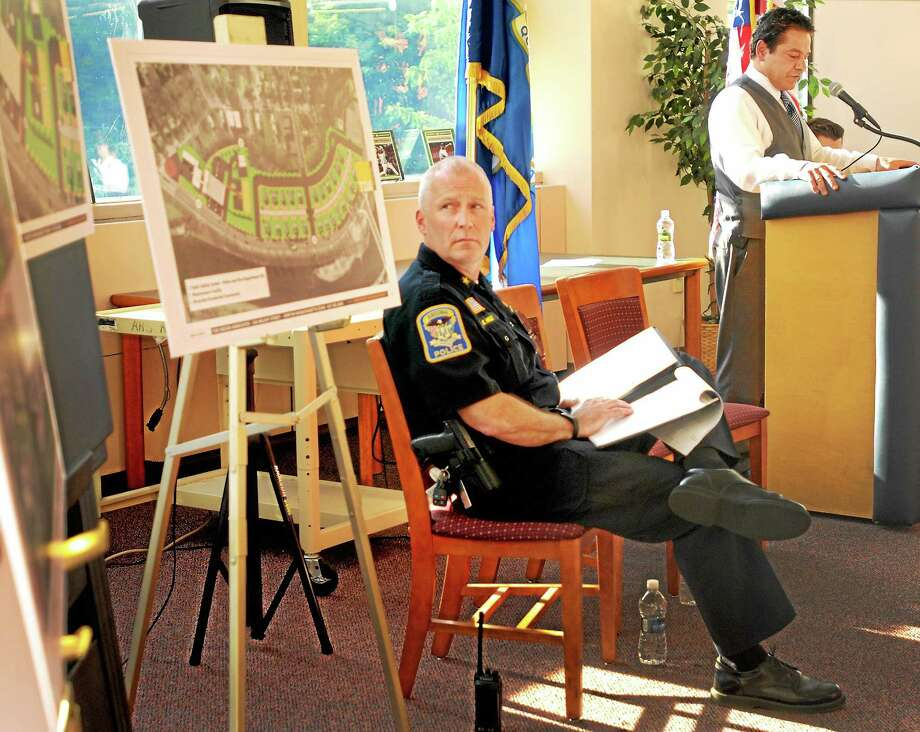 Ansonia Police Chief Kevin Hale, left, looks at architectural drawings as Ansonia Mayor David S. Cassetti, right, announces plans for revitalization of the site of the former Riverside Apartments on Olson Drive during a town meeting Thursday at Ansonia High School. Photo: Peter Hvizdak — New Haven Register     / ©Peter Hvizdak /  New Haven Register
