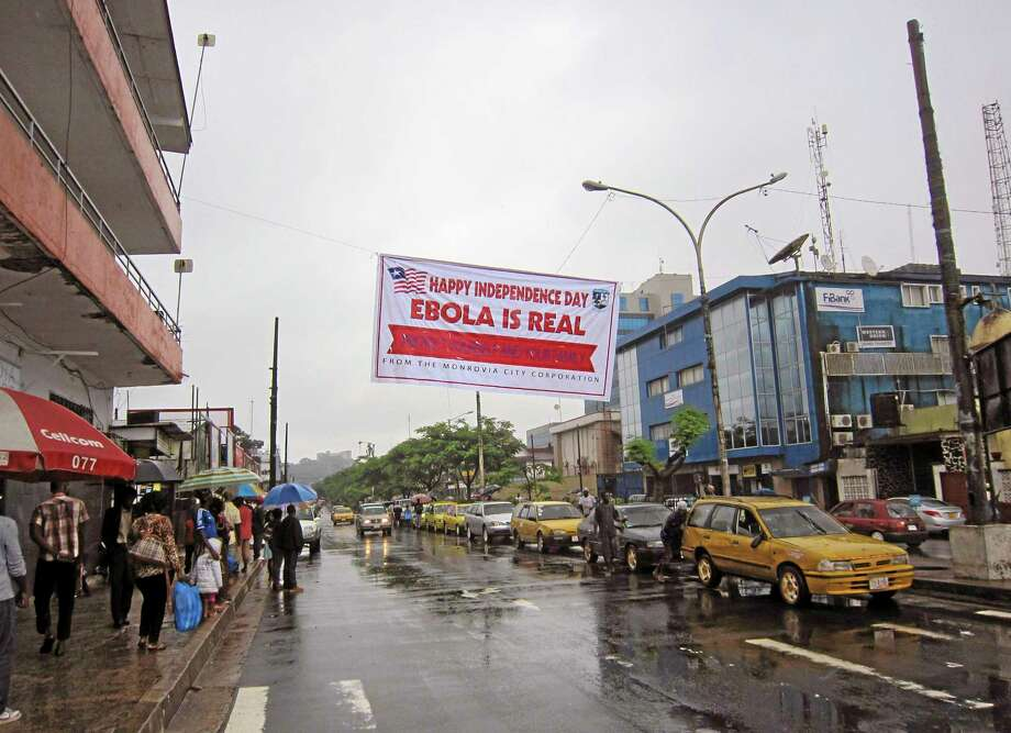 In this photo taken on Monday, July 28, 2014, people hang out in a street under a  banner which warns people to be cautious about Ebola, in Monrovia, Liberia. Two American aid workers in Liberia have tested positive for the virus and are being treated there. U.S. health officials said Monday that the risk of the deadly germ spreading to the United States is remote. (AP Photo/Jonathan Paye-Layleh) Photo: AP / AP