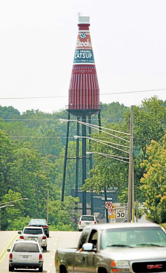 """A 170-foot giant ketchup bottle, billed as the """"World's Largest Bottle of Catsup,î and once served as a water tower is seen Tuesday, July 22, 2014, in Collinsville, Ill. A ìFor Saleî has been placed in front of the landmark that replicates a bottle of Brooks Old Original Rich and Tangy Catsup, which was produced in the buildings beneath the tower. The 100,000-gallon tower held water _ never ketchup _ and hasn't been used since Brooks moved out in the early 1960s.  (AP Photo/Belleville News-Democrat, Derik Holtmann) Photo: AP / Belleville News-Democrat"""
