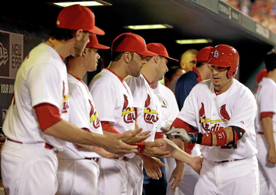 Cardinals' Allen Craig, right, is congratulated by teammates in the dugout after hitting a solo home run during the fifth inning against the New York Yankees. Photo: Jeff Roberson — The Associated Press   / AP