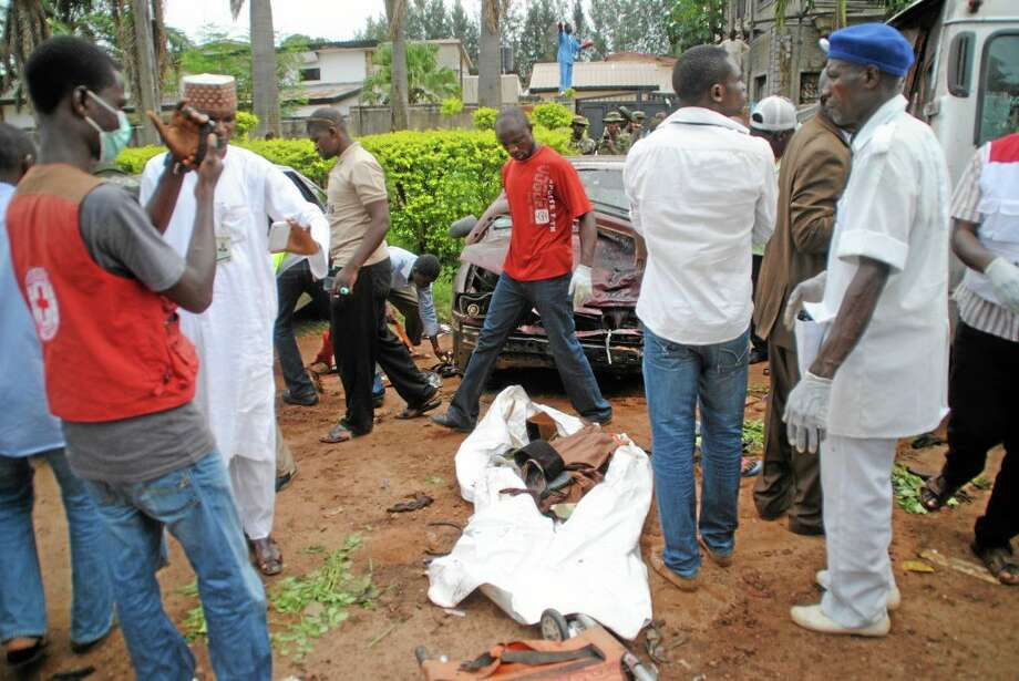 Rescue workers gathered  at the scene of an explosion in Kaduna, Nigeria. Wednesday, July 23, 2014. Police say at least 25 people were killed Wednesday by two bombings in the northern city of Kaduna. Police Commissioner Umar Usman Shehu said the first blast came after Sheik Dahiru Bauchi gave an annual Ramadan speech for thousands of faithful in an outdoor service. Sheik Bauchi is known for preaching against the violent extremism of Nigeria's Islamic militants, Boko Haram. (AP Photo) Photo: AP / AP