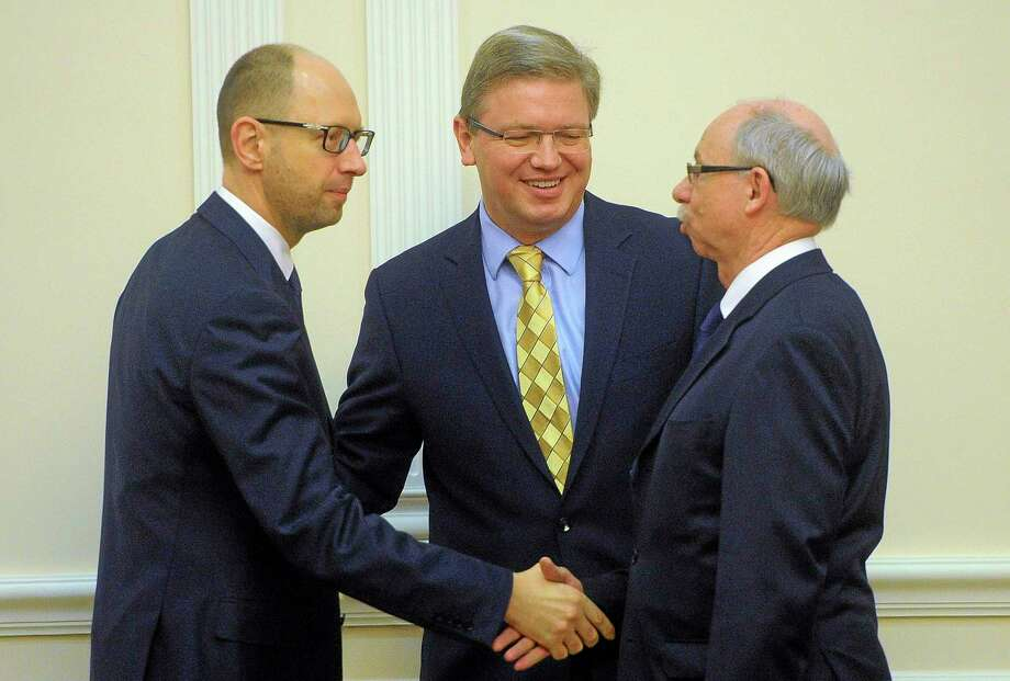 Ukrainian Prime Minister Arseniy Yatsenyuk, left,  welcomes European Commissioner for Enlargement and European Neighborhood Policy Stefan Fule, center, and EU Commissioner designate for Budget Janusz Lewandowski , right, in Kiev, Ukraine, Thursday, March. 26, 2014.(AP Photo/Andrew Kravchenko, Pool) Photo: AP / AP