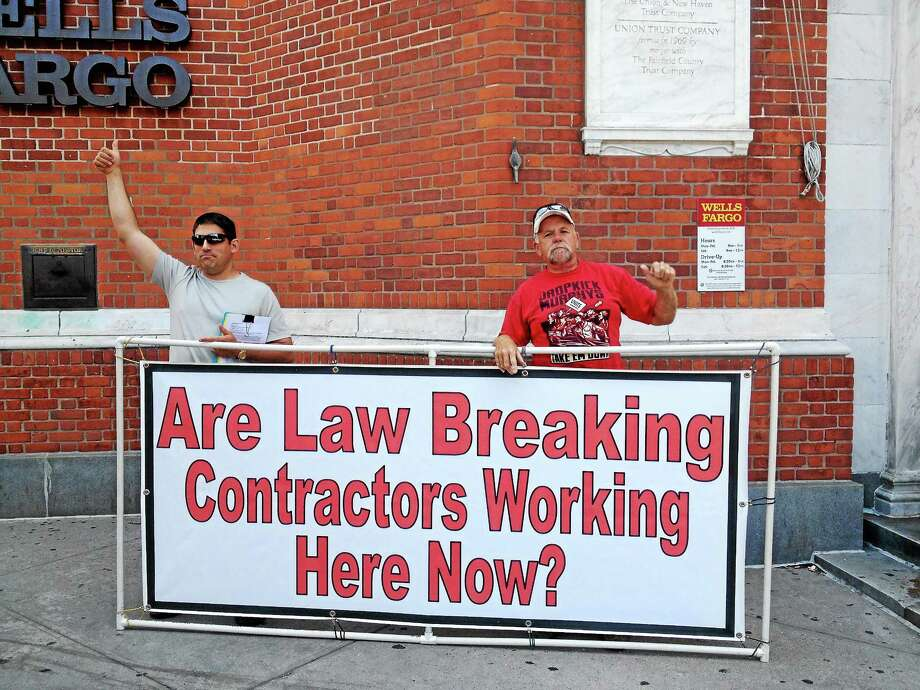 Tim Sullivan and David Jarvis of the New England Regional Council of Carpenters protest Regional Wall Systems, a Florida subcontractor performing work at the Cooper Square apartment conversion at 205 Church St., because of a stop-work order Friday for failing to produce payroll records. Photo: Kristin Stoller — New Haven Register