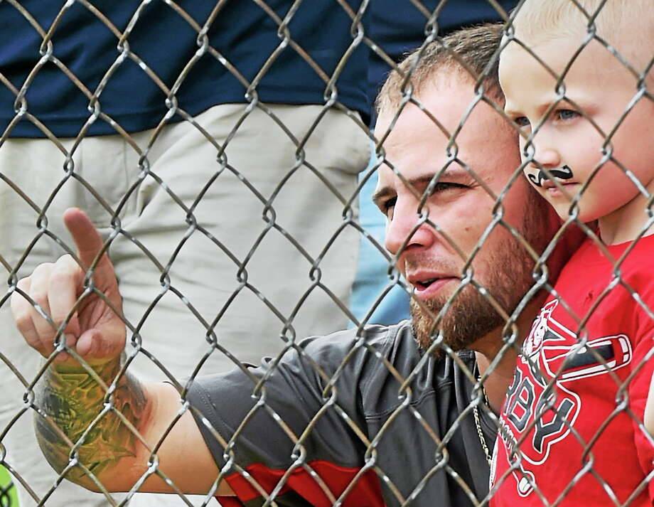 """Fans look through a fence watching the """"rematch"""" of the 1889 Ansonia Coppermen-Derby Osborndales game 7/19. Photo: (Melanie Stengel — Register)"""