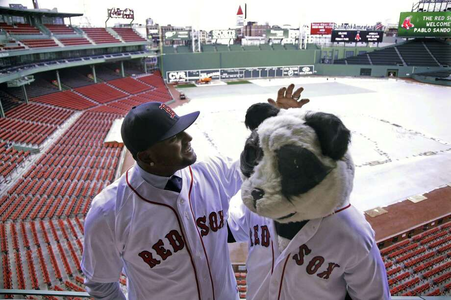 Newly acquired Boston Red Sox third baseman Pablo Sandoval, nicknamed Kung Fu Panda, converses with a person dressed as a panda bear wearing a Red Sox jersey, overlooking a snow-covered Fenway Park on Tuesday in Boston. Photo: Stephan Savoia — The Associated Press   / AP