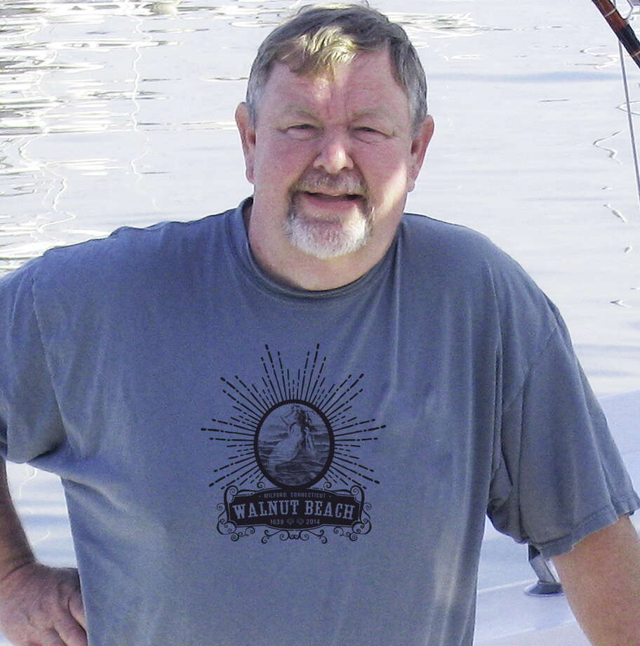 An unidentified volunteer wears a T-shirt like the ones that registered participants walking in the Walnut Beach Float parade will receive. Photo: Journal Register Co.