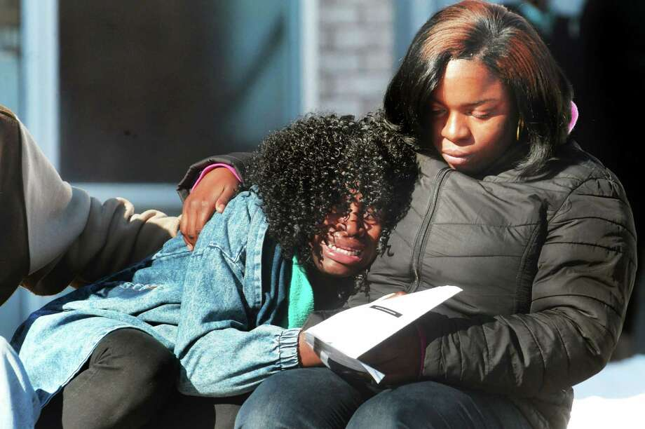 Mourners comfort one another after the funeral service for Durell Patrick Law Wednesday in New Haven. Photo: VM Williams — New Haven Register