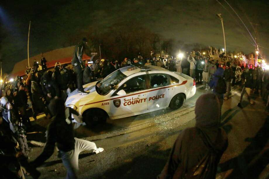 A protester squirts lighter fluid on a police car as the car windows are shattered near the Ferguson Police Department after the Nov. 24, 2014 announcement of the grand jury decision not to indict police Officer Darren Wilson in the fatal shooting of Michael Brown, an unarmed black 18-year-old, in Ferguson, Mo. Photo: AP Photo/Charlie Riedel   / AP