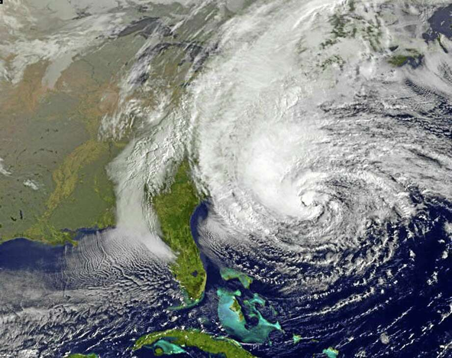 This NOAA satellite image taken Sunday, Oct. 28, 2012, shows Hurricane Sandy off the Mid Atlantic coastline moving toward the north with maximum sustained winds of 75 mph. Tens of thousands of people were ordered to evacuate coastal areas Sunday as big cities and small towns across the U.S. Northeast braced for the onslaught of a superstorm threatening some 60 million people along the most heavily populated corridor in the nation. (AP Photo/Weather Underground) Photo: AP / Weather Underground
