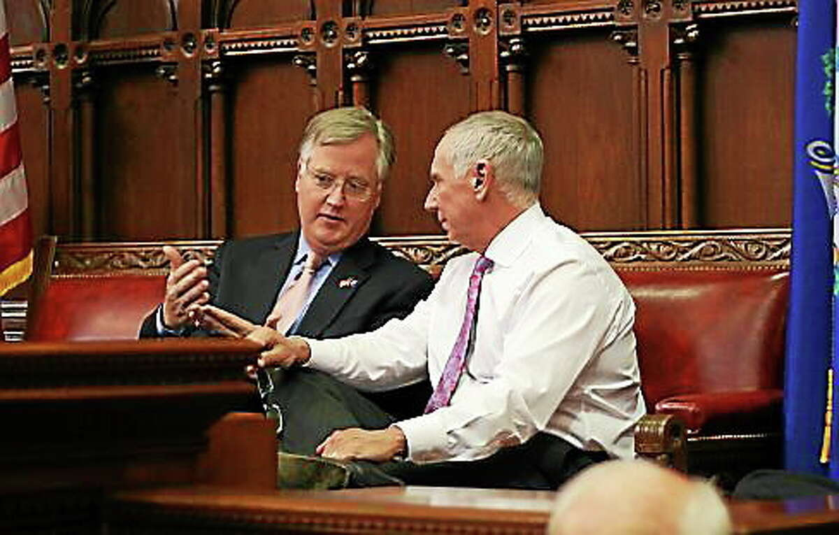 House Speaker Brendan Sharkey talks with, Mark Ojakian, the governor's chief of staff as the House debates minimum wage.