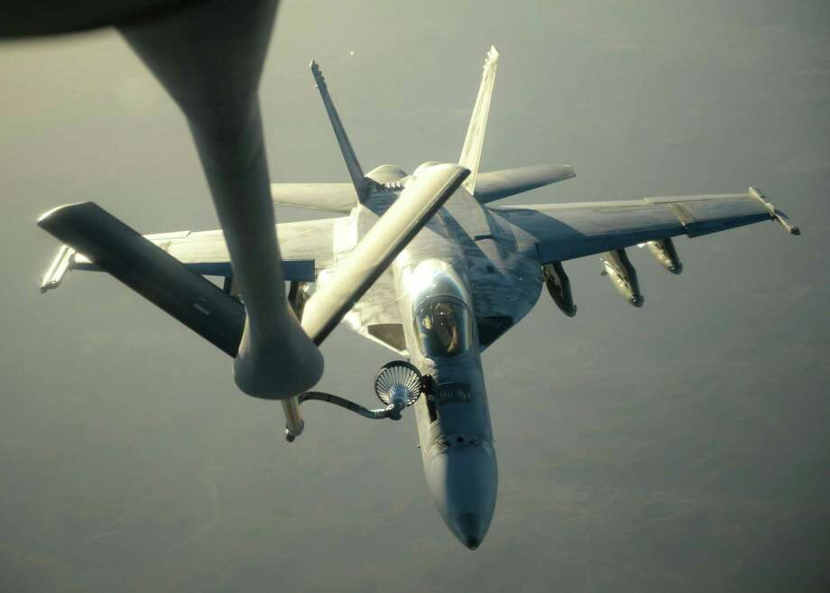 In this Tuesday, Sept. 23, 2014 photo released by the U.S. Air Force, a U.S. Navy F-18E Super Hornet receives fuel from a KC-135 Stratotanker over northern Iraq after conducting airstrikes ias part of U.S. led coalition airstrikes on the Islamic State group and other targets in Syria. U.S.-led airstrikes targeted Syrian oil installations held by the militant Islamic State group overnight and early Thursday, Sept. 25, 2014, killing nearly 20 people as the militants released dozens of detainees in their de facto capital, fearing further raids, activists said. (AP Photo/U.S. Air Force, Staff Sgt. Shawn Nickel) Photo: AP / US Air Force