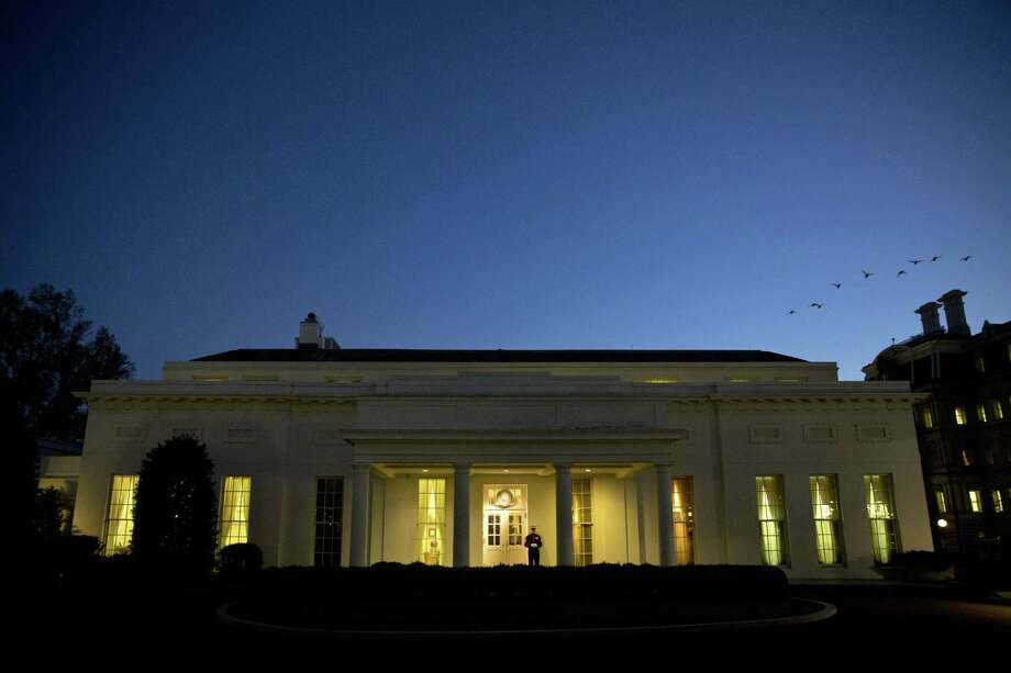 Birds fly over the West Wing of the White House at dusk on Nov. 24, 2014, in Washington. Photo: AP Photo/Jacquelyn Martin   / AP