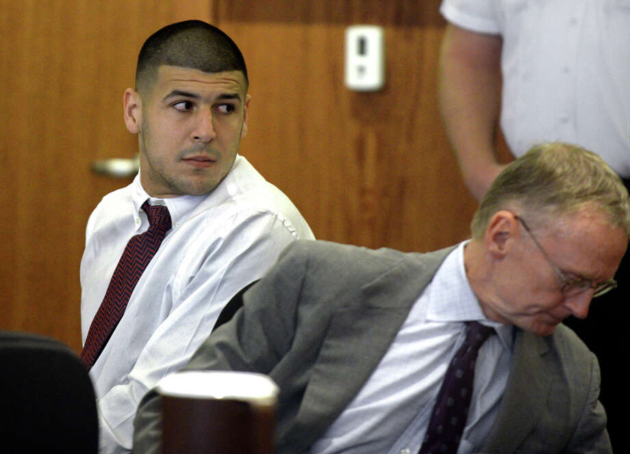 Former New England Patriots football player Aaron Hernandez, left, looks back as he sits next to his attorney Charles Rankin during a hearing in Fall River Superior Court on Sept. 30, 2014, in Fall River, Mass. Photo: AP Photo/The Boston Herald, Ted Fitzgerald, Pool   / Pool The Boston Herald