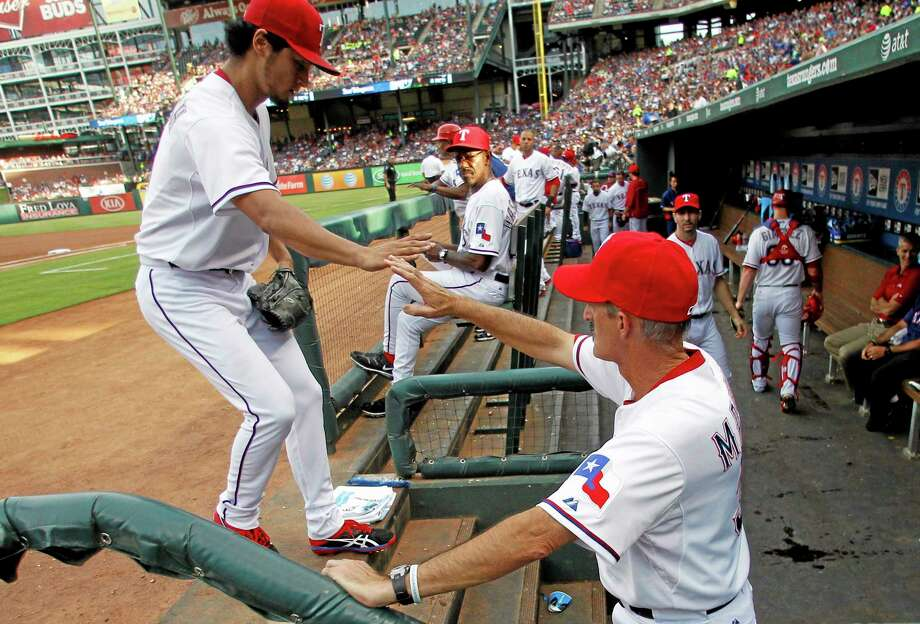 Rangers starting pitcher Yu Darvish, left, is greeted in the dugout by pitching coach Mike Maddux, right, after working against the New York Yankees in the first inning Monday. Photo: Tony Gutierrez  — THE ASSOCIATED PRESS   / AP