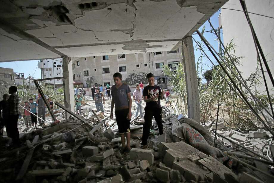 Palestinians inspect the rubble of a destroyed house following an Israeli strike killing Christian woman Jalila Ayyad, 70, in Gaza City on Sunday, July 27, 2014. (AP Photo/Khalil Hamra) Photo: AP / AP