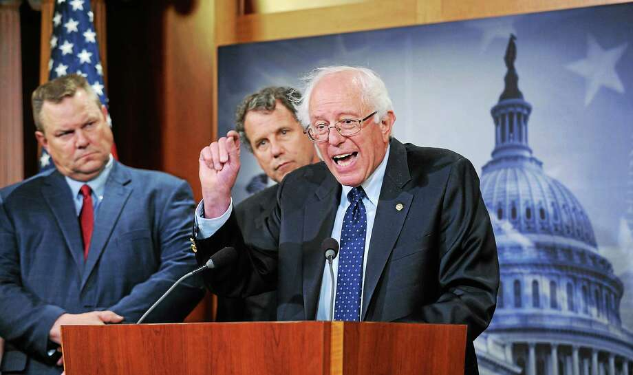 Sen. Bernie Sanders, I-Vt., right, joined by Sen. Jon Tester, D-Mont., left, and Sen. Sherrod Brown, D-Ohio, center, speaks during a news conference on Capitol Hill in Washington on July 24, 2014, about the Veterans Administration. Photo: AP Photo   / AP