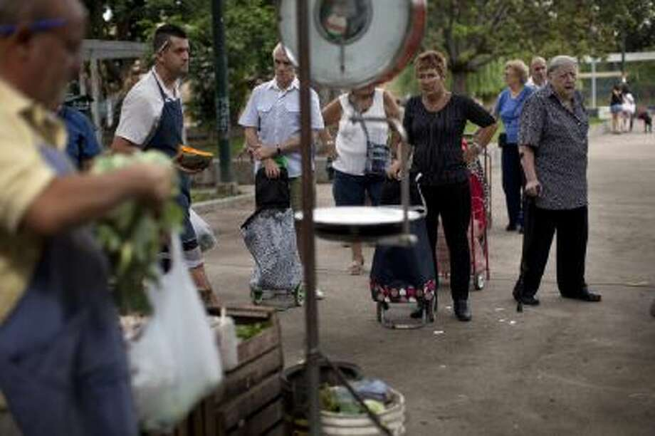 People wait in line for their turn to buy fruit and vegetables at a market in Buenos Aires, Argentina, Wednesday, Jan. 29, 2014. The market is organized by the city?s municipal government and offers consumers lower food prices. With Argentina?s peso on its sharpest slide in 12 years since the economic collapse of 2001-2002, Argentines are dealing with one of the world's highest inflation rates.