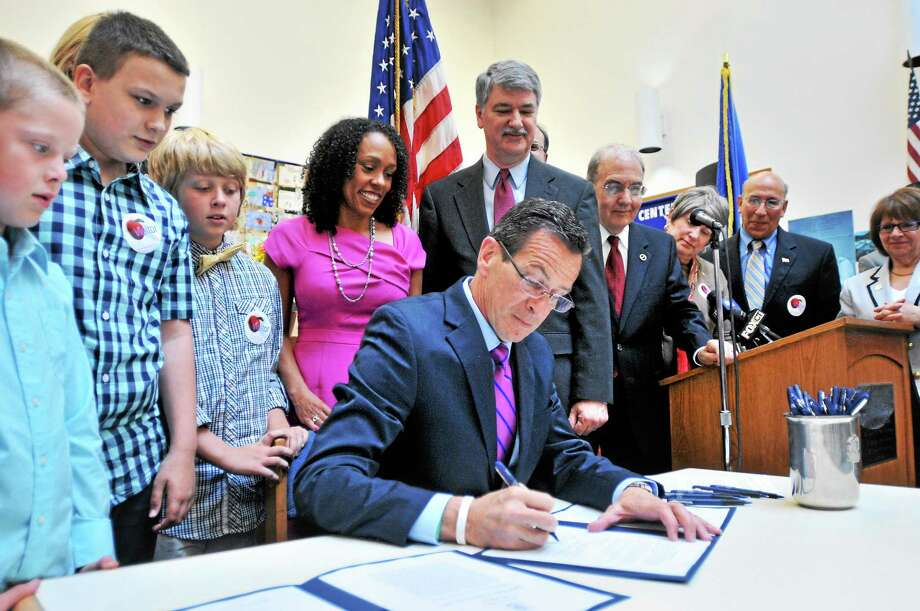Gov. Dannel P. Malloy, center, signs Public Acts No. 14-39 and 14-41 expanding pre-kindergarten for 3- and 4-year-olds and establishing the Office of Early Childhood at the Helen Street School in Hamden Wednesday. Photo: Arnold Gold — New Haven Register